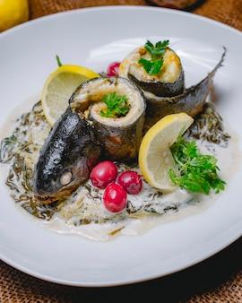 Ryba walcowana w kremowym sosie szpinakowym widok z boku pietruszki cytrynowej cytryny