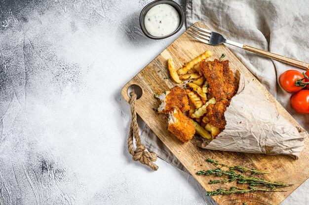 Ryba z frytkami, brytyjskie fast foody podawane z sosem tatarskim. szara powierzchnia. widok z góry. skopiuj miejsce