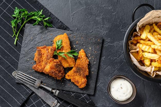 Ryba z frytkami, frytki i filet z dorsza smażone w bułce tartej. widok z góry