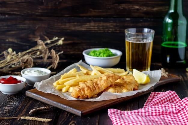 Ryba z frytkami na drewnianym. brytyjskie fast foody. przepisy przekąska do piwa. kuchnia angielska.