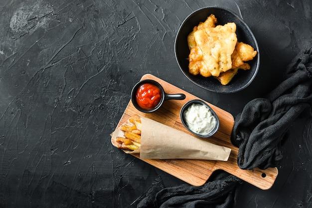 Ryba z frytkami w papierowym rożku na desce do krojenia dip i cytryna