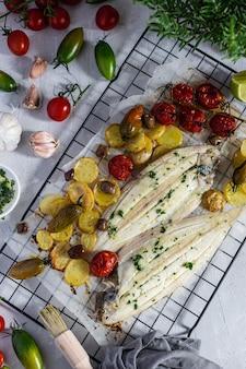 Ryba z soli z grilla z zielonymi i czerwonymi pomidorami cherry, ziemniakami, kaparami, czosnkiem, natką pietruszki i oliwą z oliwek