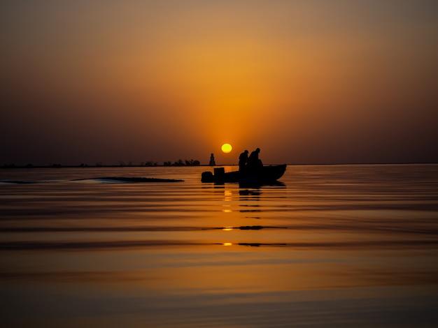 Rybacy w łodzi rybackiej na złoty zachód słońca na morzu.