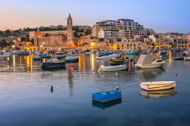 Rybak i łodzie pasażerskie w marsaskala zatoce na malta w wieczór