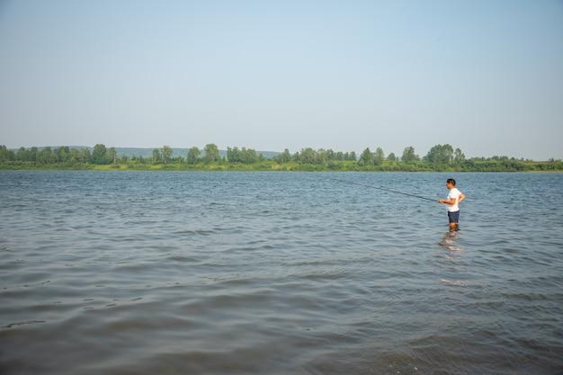 Rybak łapie rybią pozycję w wodzie rzeczny tom w kemerovo, syberia, rosja