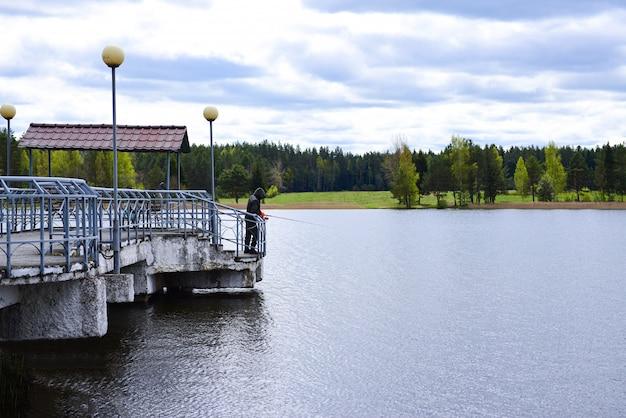 Rybak łowi na jeziorze z betonowego molo