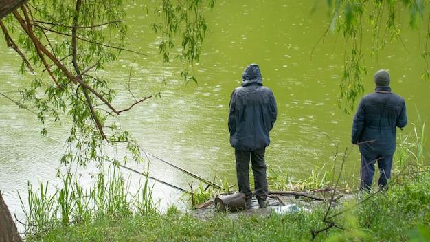 Rybak łowi ryby w jeziorze na wędkę podczas deszczu.