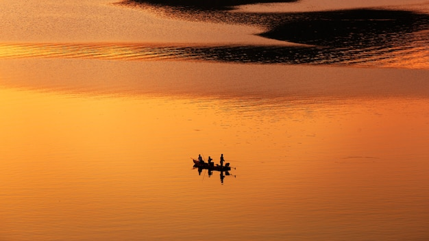 Rybak łowiący z łodzi na jeziorze o zachodzie słońca