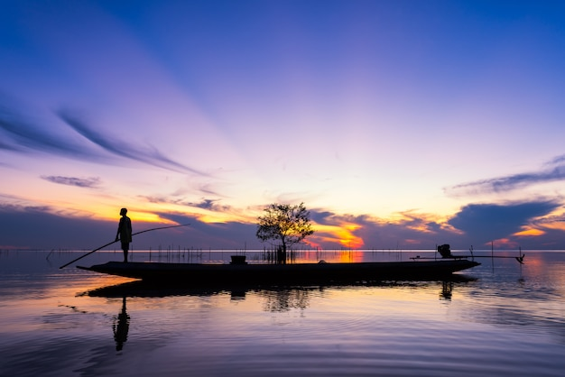 Rybak na długiego ogonu łodzi w jeziorze na wschodzie słońca przy pakpra wioską, phatthalung, tajlandia