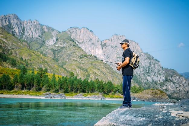 Rybak na halnej rzece przy ładnym letnim dniem. pstrąg latać połowów w rzece górskiej z górami
