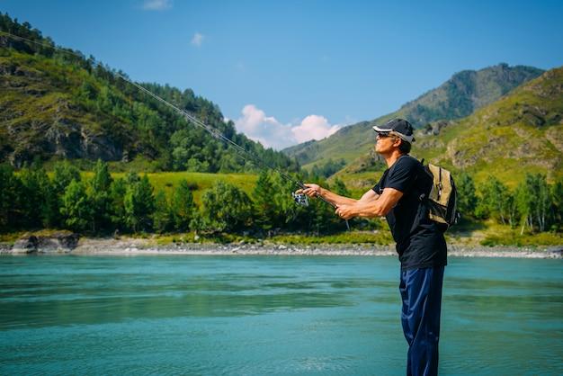 Rybak na halnej rzece przy ładnym letnim dniem