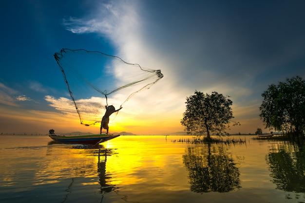 Rybak na łodzi łapanie ryba z wschodem słońca