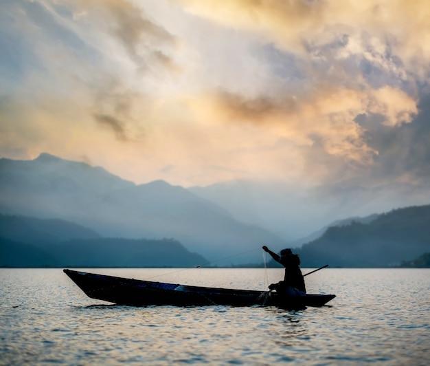 Rybak na łodzi łowiący ryby o zachodzie słońca