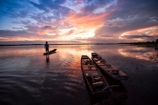 Rybak na łodzi rybackiej sylwetki zmierzchu lub wschodzie słońca w rzecznym jeziornym pięknym niebie