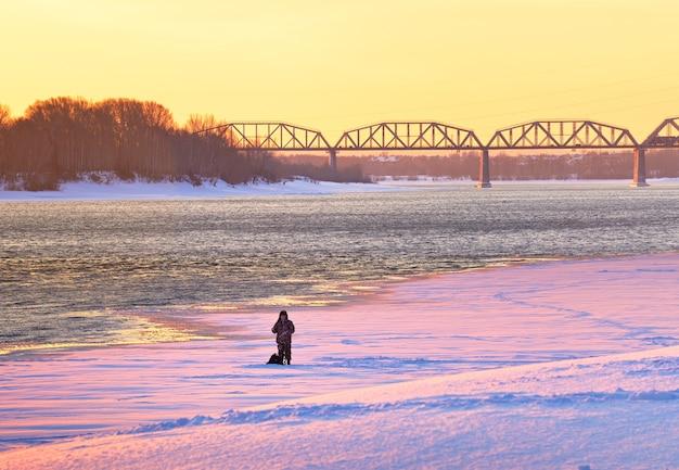 Rybak na lodzie mostu kolejowego na rzece ob