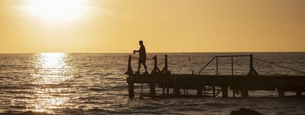Rybak na molo o zachodzie słońca, baner z miejscem na kopię