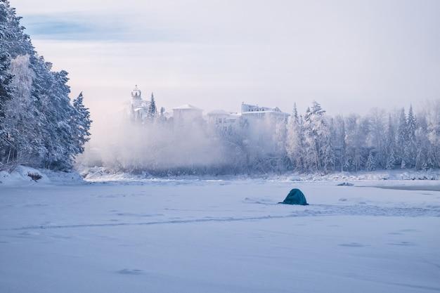 Rybak na zamarzniętej rzece wziął schronienie w namiocie.