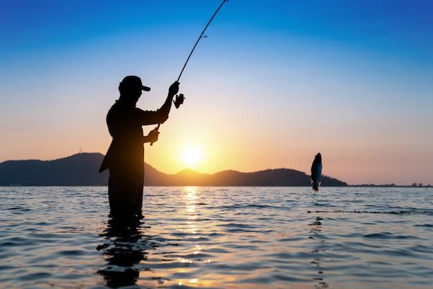 Rybak rzuca swoją wędkę, łowiąc w jeziorze, scena piękny zachód słońca rano.