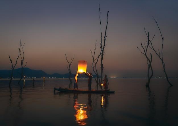 Rybak spławowa lampa na drewnianej łodzi w jeziorze.