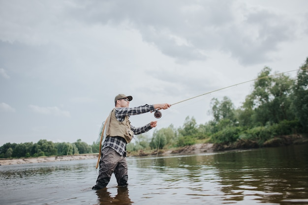 Rybak stoi w płytkiej wodzie i łowi ryby. za to rzuca łyżeczką do przodu. facet trzyma w ręce wędkę. on tego używa. mężczyzna nosi wodery, kamizelki i czapki, aby chronić ciało.