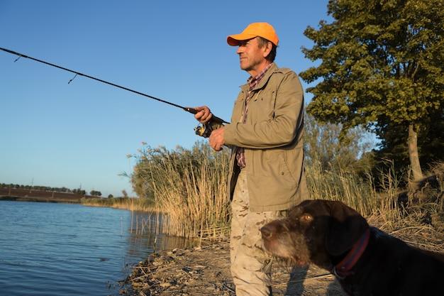 Rybak stojący nad brzegiem rzeki i próbujący złapać rybę. sport, rekreacja, styl życia.