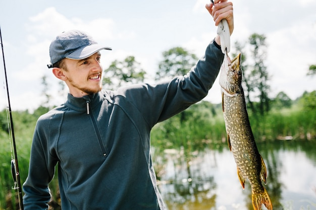 Rybak trzyma dużego rybiego szczupaka na tle jeziora i natury. tło wędkowanie.
