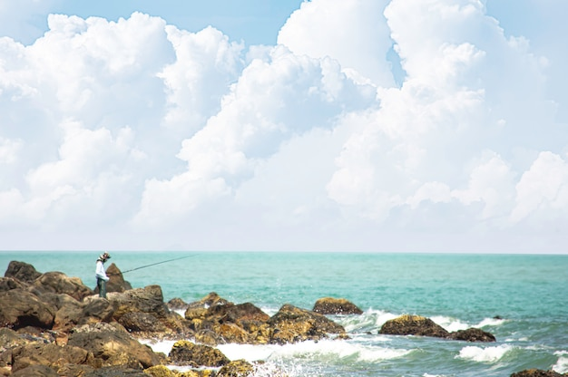 Rybak trzyma połowu prącie na skałach morzem przy laem kho kwang plażą w chumphon, tajlandia.
