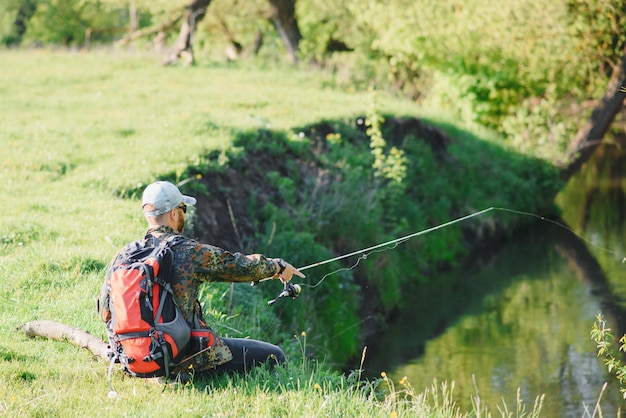 Rybak wędkarski wędką spinningową na brzegu rzeki, spinning, łowienie ofiar
