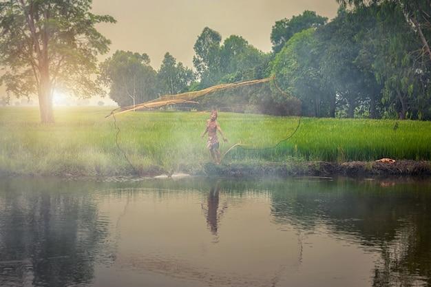 Rybak wysiewający suche sieci rybackie przy zmierzchem przy jeziorem w tajlandia.