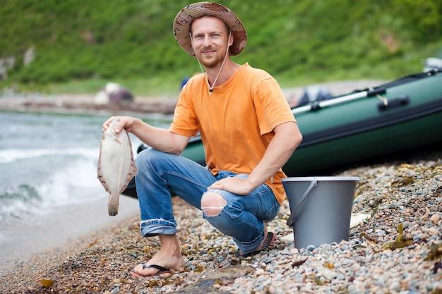 Rybak z płastugą w ręku nad morzem