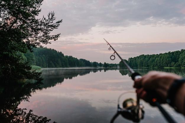 Rybak z prętem, przędzenia rolka na brzegu rzeki. wędkowanie na szczupaka, okonia, karpia. dzika natura.