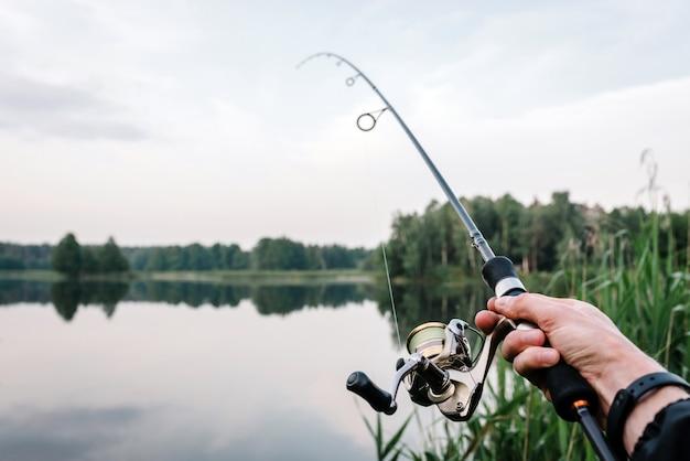 Rybak z prętem, przędzenia rolka na brzegu rzeki. wędkowanie na szczupaka, okonia, karpia. mgła na tle jeziora.