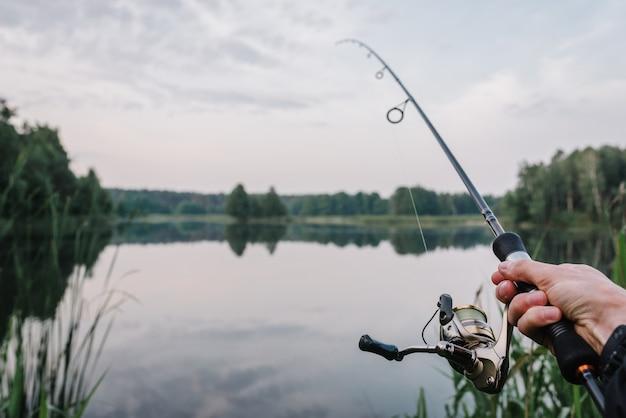 Rybak z przędzalnianą rolką na brzeg rzeki. wędkowanie na szczupaka, okonia, karpia.