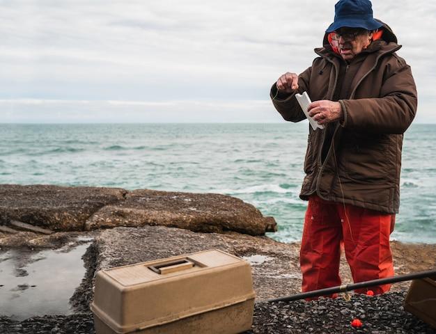 Rybak z pudełkiem na sprzęt wędkarski