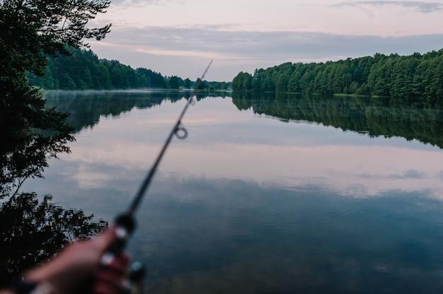 Rybak z wędką, przędzenia rolki na brzegu rzeki w tle.
