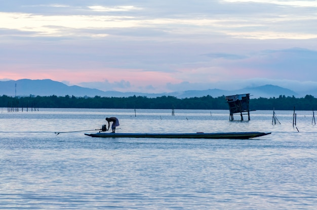 Rybak zaczyna silnika drewniana łódź w jeziorze