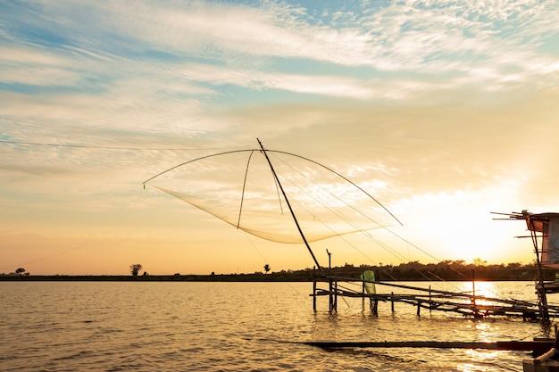 Rybaka narzędzia połowowe w jeziorze przy zmierzchu niebem.