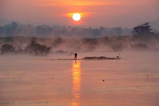 Rybaka połów na rzece w światło słoneczne ranku, sylwetka rybak na łodzi.