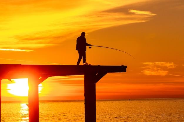 Rybaka połów w morzu na molu przy zmierzchem