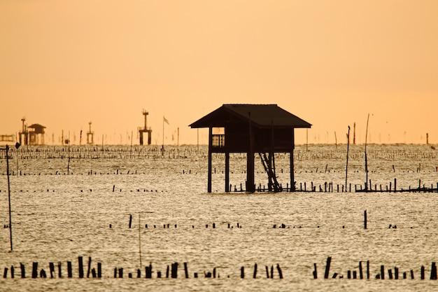 Rybaków drewniani domy przy wschodem słońca w morzu
