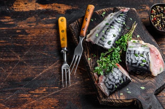 Rybę wędzoną makrelę kroimy z ziołami. ciemne drewniane tło. widok z góry. skopiuj miejsce.