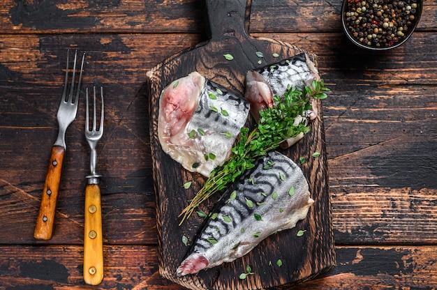 Rybę wędzoną makrelę kroimy z ziołami. ciemne drewniane tło. widok z góry.