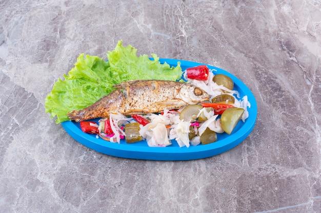 Ryby i różne konserwy warzywne na drewnianym talerzu, na marmurze.