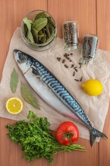 Ryby morskie (makrela) i przyprawy na podłoże drewniane. widok z góry.