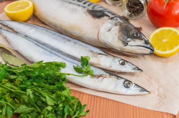Ryby morskie (makrela, saury) i przyprawy na podłoże drewniane. widok z góry.