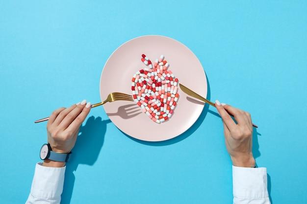 Ryby z kolorowych pigułek i tabletek na białym talerzu, dłonie dziewczyny z zegarkiem na niebieskiej ścianie z cieniami, miejsce na kopię. negatywny wpływ tabletek na choroby sercowo-naczyniowe. widok z góry.