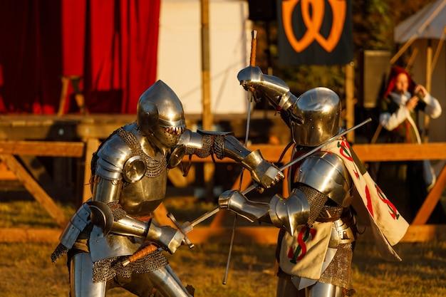 Rycerze w średniowiecznych zbrojach walczą na turnieju w lecie. zdjęcie wysokiej jakości