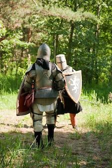 Rycerze w zbroi walczą w lesie
