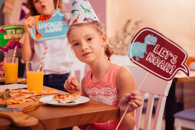 Ryczmy. słodkie dziecko, trzymając uśmiech na twarzy, siedząc przy stole