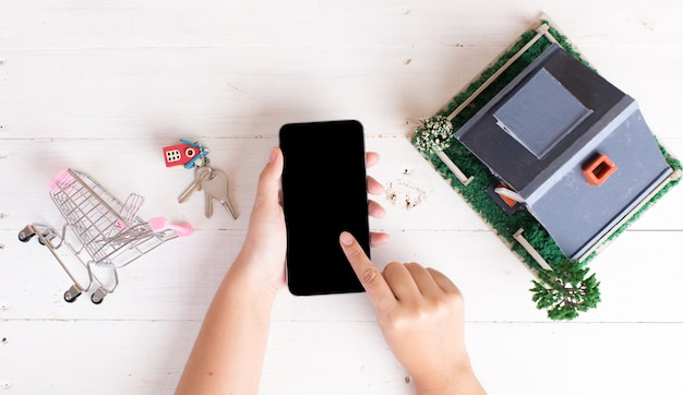 Rynek nieruchomości z kluczami do domu, koszykiem i telefonem
